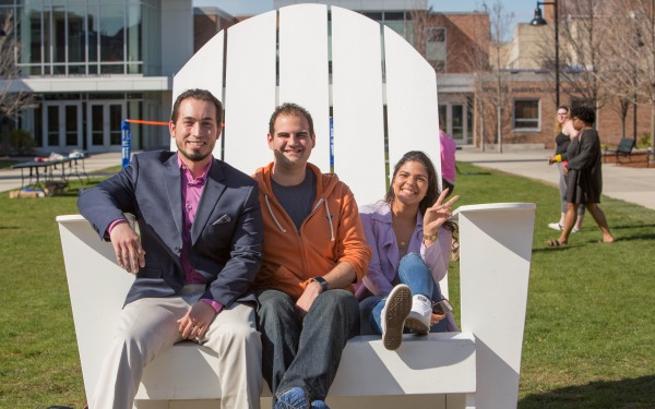 Students in a large chair on the quad