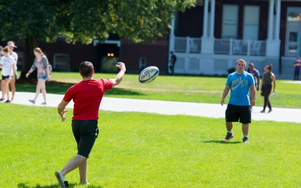 studnets toss a football on the quad