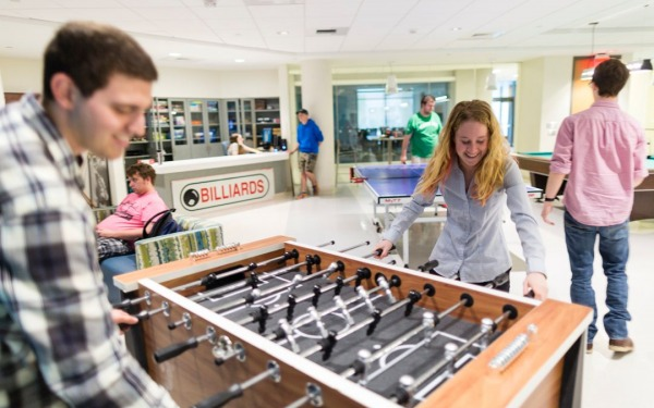 Students playing foosball in the campus game room