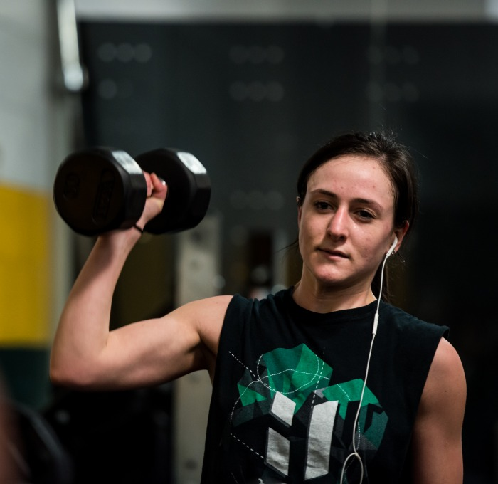 a female student lifts weights in the rec center