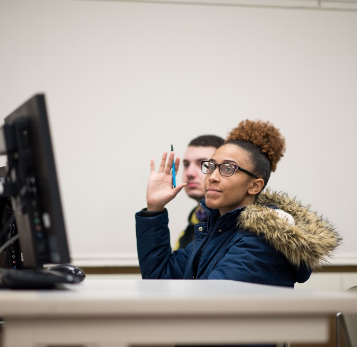 Student raises her hand in computer science class