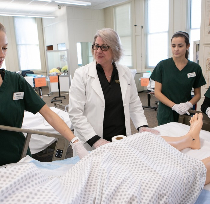 Students care for a patient in a nursing classroom