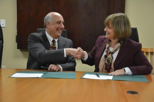 President Lapidus and Anna Clementi shake hands after signing the memorandum of agreement…